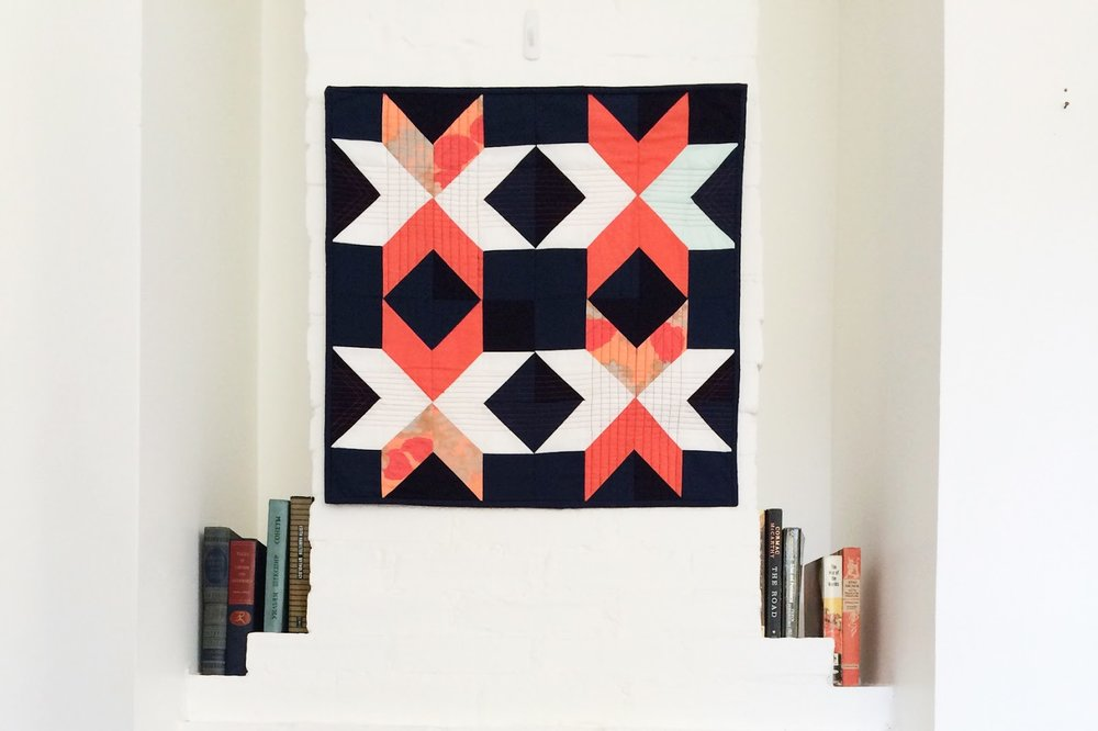 Dark Star coral and navy modern wall quilt living in its Mississippi home | by Lovely and Enough