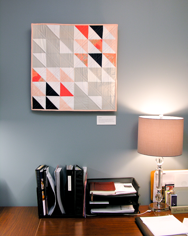 Little Pieces coral and navy modern wall quilt living in its Wheaton College home | by Lovely and Enough