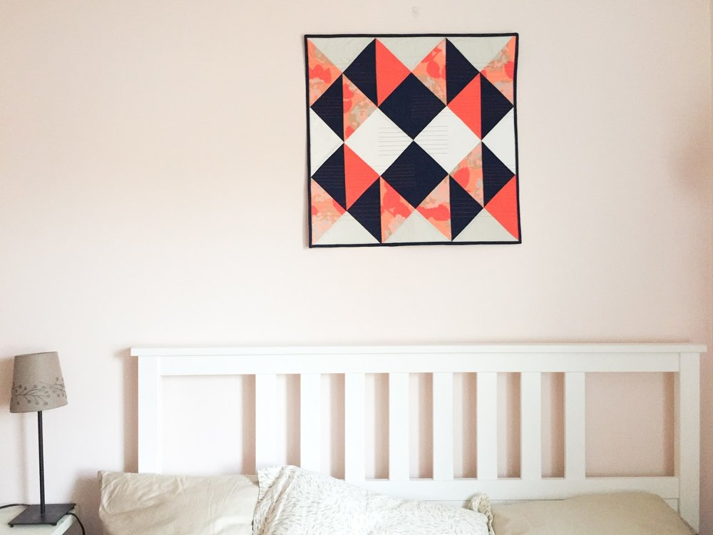 Modern Buckwheat coral and navy wall quilt living in its Boston home | by Lovely and Enough