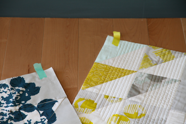 two modern quilts in hand-printed fabric with screen-printing over top