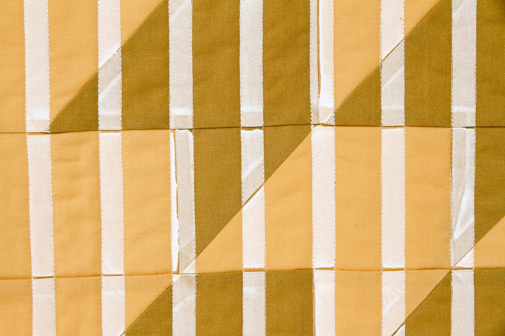 mustard Lenten Twelves One modern quilt printed with stripes, quilted and faced