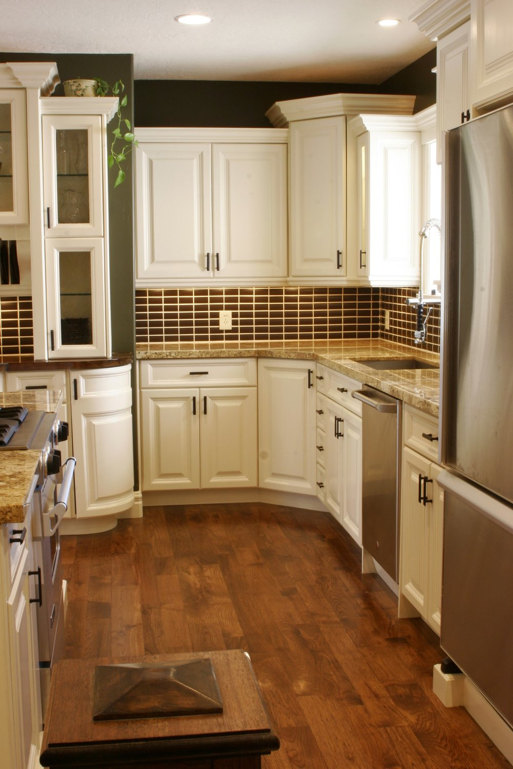 Rustic Hickory floorts were stained dark for a more uniform color to contrast the cream colored cabinets