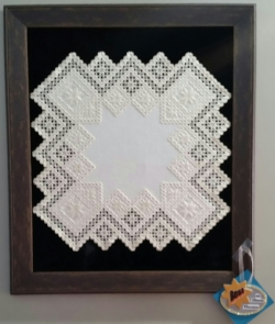 "This is the piece selected for best of show for the art club's theme for this year, which was  ""Geometric Shape"".  This is a textile,  Hardanger,  a Norwegian cross stitch with cut outs by Priscilla Magaardan Andrews."