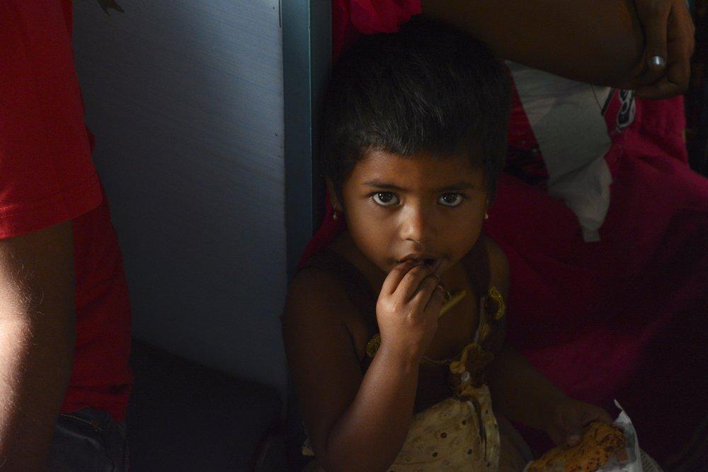 Girl eating vada on train.