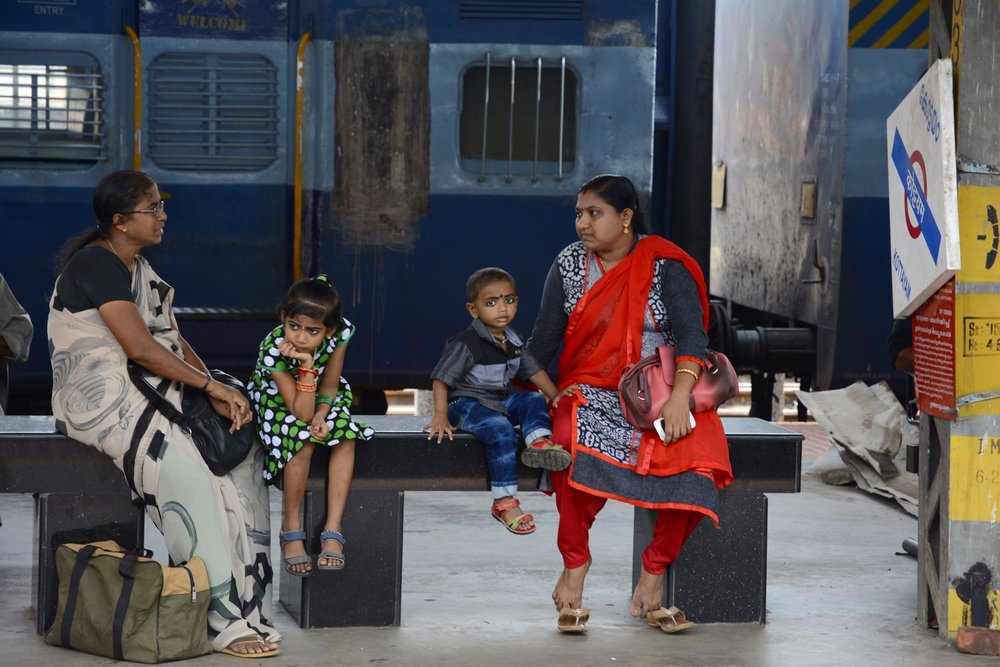Mother and children at train station.