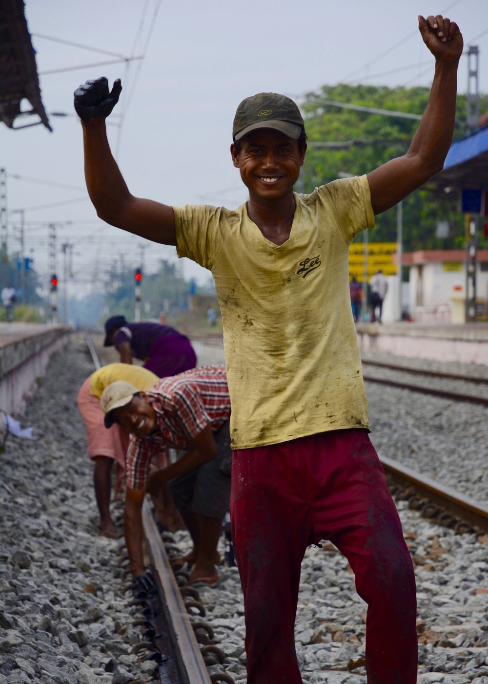 Young workers greasing tracks with bare hands.