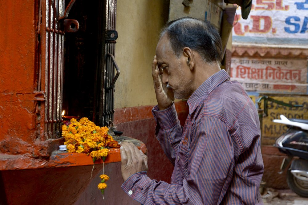 In prayer at a shrine behind the ghats.
