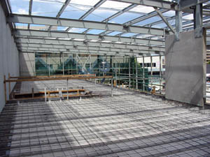 Steel reinforcement to concrete mezzanine slab, structural steel including portal frames and precast panels.