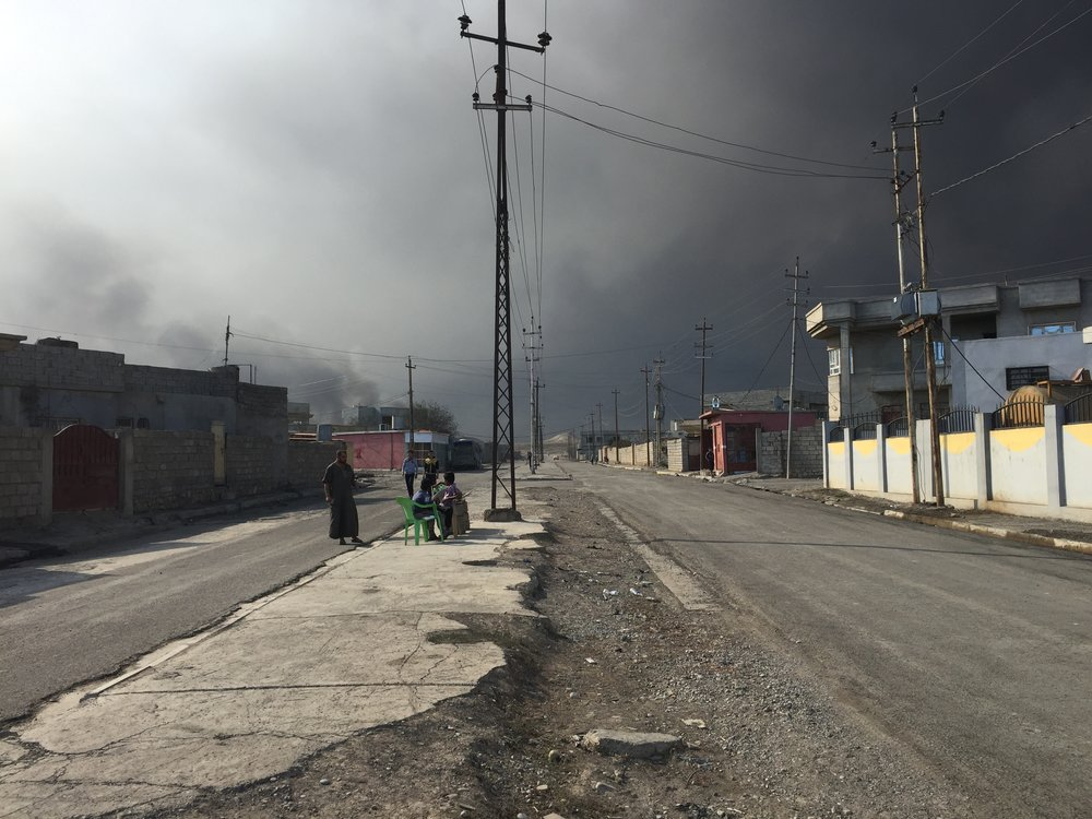 QAYARA | Residents living in Qayara under a cloud of black smoke. ISIS set 19 oil wells on fire in August. November 3, 2016.