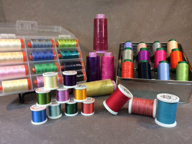 Pictured here (back row, l to r) is an Aurifil thread set, Mettler Seracor polyester thread for quilting and longarm machines, and an assortment of Isacord embroidery threads. (Front row, l to r) YLI silk thread, and YLI quilting thread.