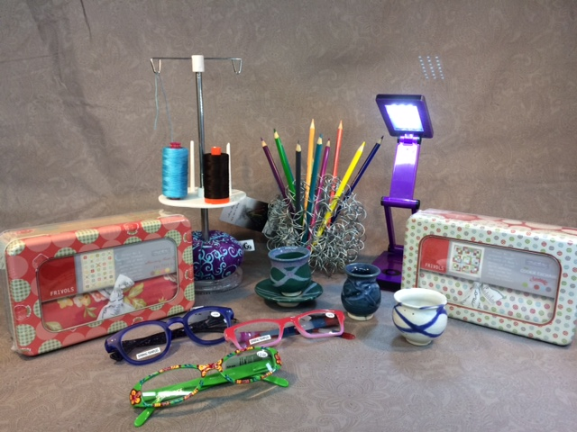 Whimsical, fun, and practical: Frivols tinned quilt kits, colorful readers, a pincushion-threadstand combo, a crazy wire ball pen and pencil holder, a portable free-standing light, and mini pots and saucers from Whitefish Pottery.
