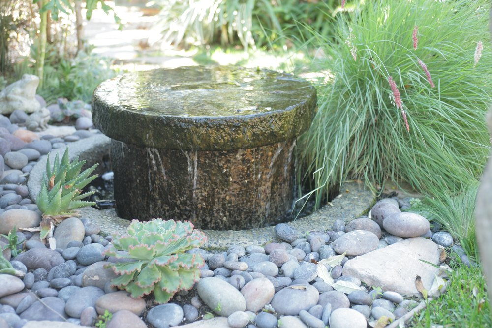 Fountain made from a millstone with grasses and succulents.