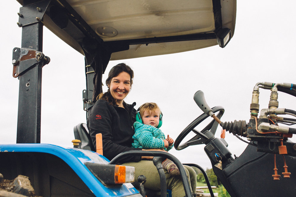 Title:  Amelia Bright on a tractor with her daughter Hazel, Amber Creek Farm, Fish Creek, 2016  Source:  Museums Victoria  Photographer:  Catherine Forge