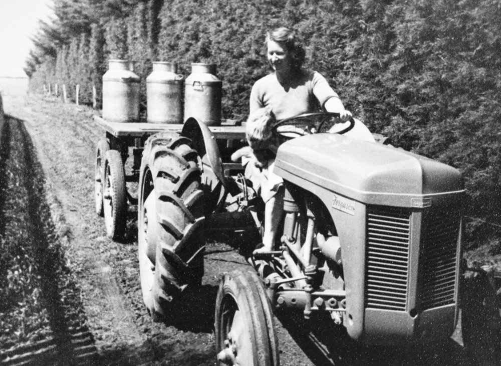 Title:   Women with Milk Churns on Ferguson Tractor , Cobden District, Victoria, circa 1950: The Biggest Family Album in Australia  Source:  Museums Victoria  Photographer:  Unknown