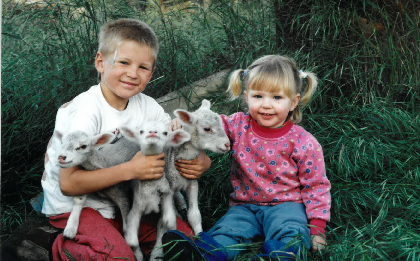 Young Emily and her brother with lambs on the family farm, image supplied.
