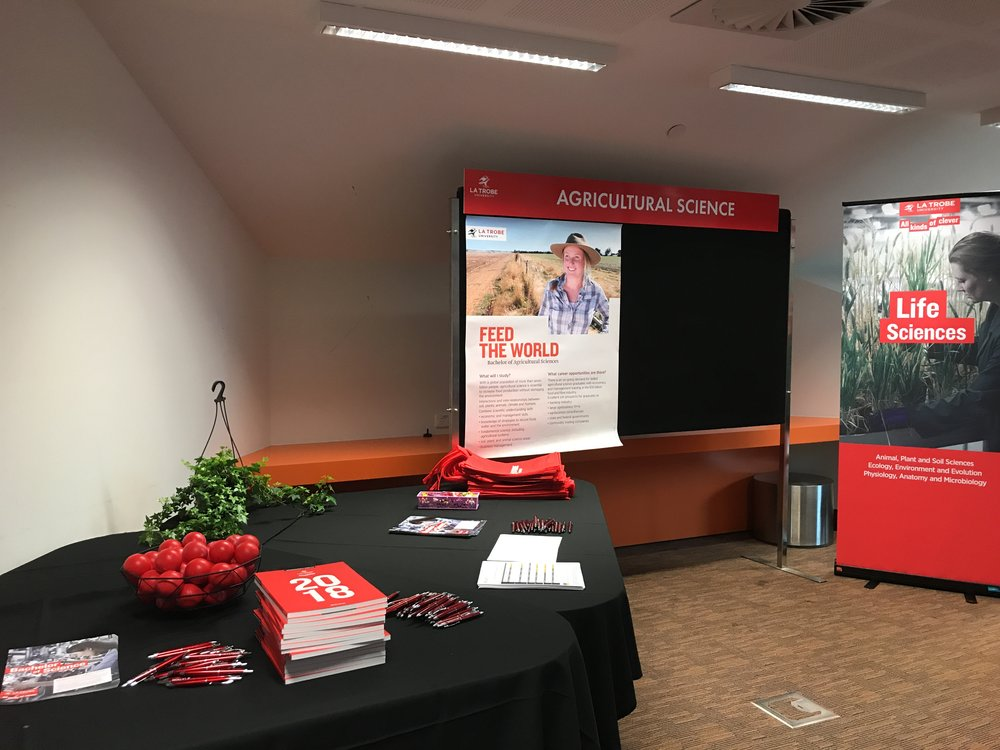 "A photo during Rayali's studies at La Trobe University: ""This photo shows a stall that I set up at La Trobe. Along with my course co-ordinator and professors, I attended the La Trobe open day where I was speaking to students from year 10-12 about careers in Ag and advocating for the Ag Science degree at La Trobe (one of the best ones going around)!"""