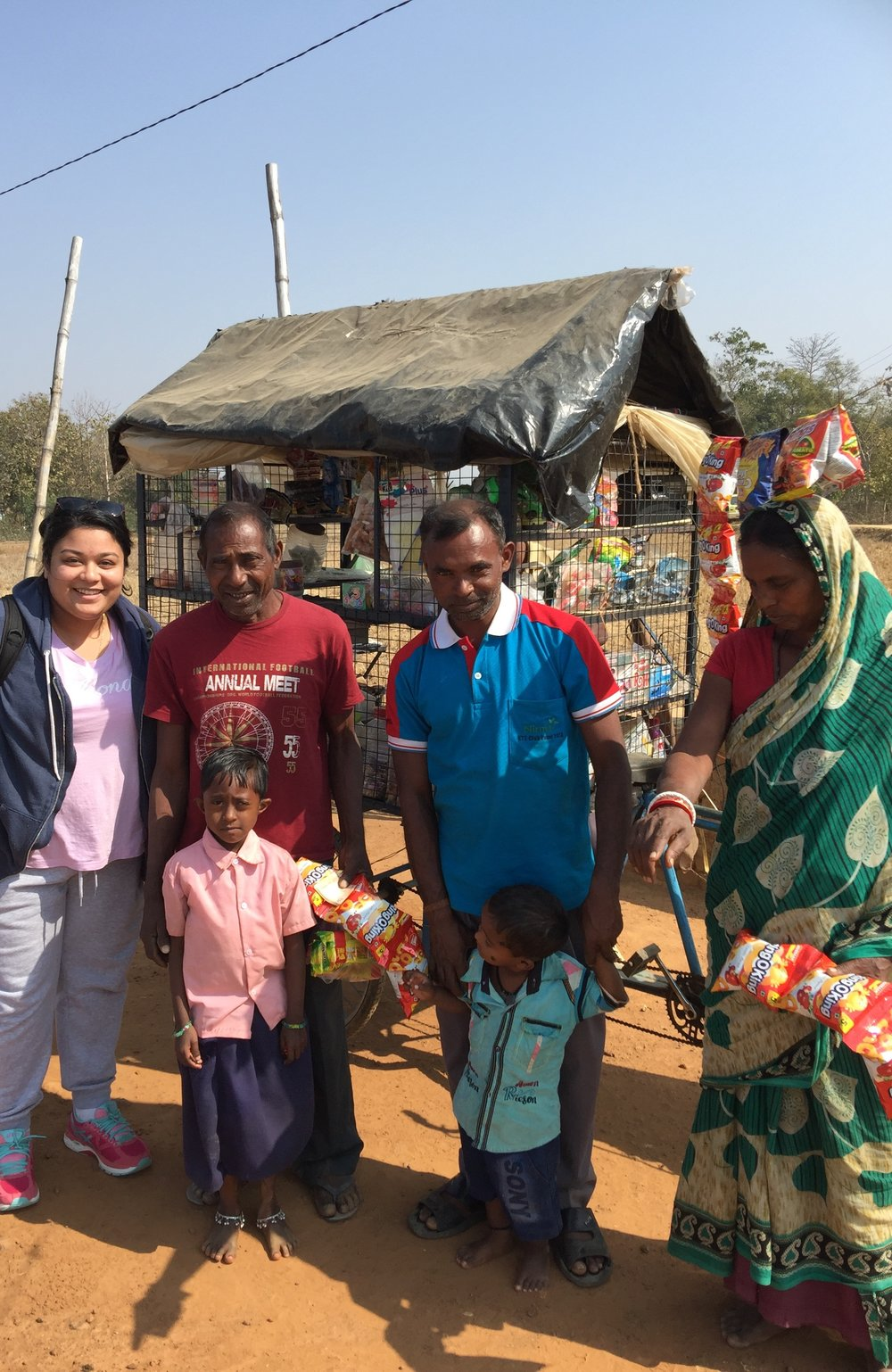 """The village Panchpir where I was working with smallholder farmers. In this photo, I had just bought the kids some chips and chocolate (shop pictured behind us)."""