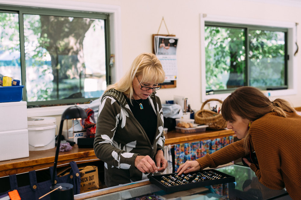 Sally Hall showing Catherine Forge her jewellery creations, Mountain Fresh Trout and Salmon Farm, Harrietville (Victoria), 2018, Photographer: Fiona McLennan.