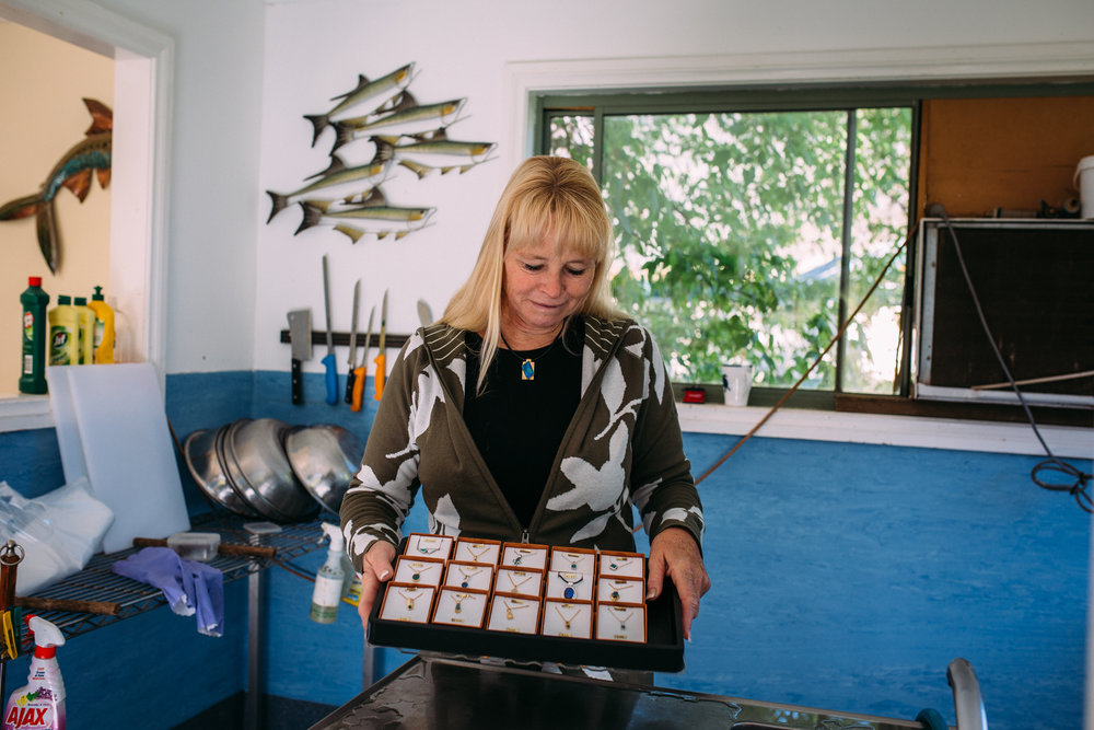 Sally Hall in her Farm Gate store with opals and fish in the background, Mountain Fresh Trout and Salmon Farm, Harrietville (Victoria), 2018, Photographer: Catherine Forge.