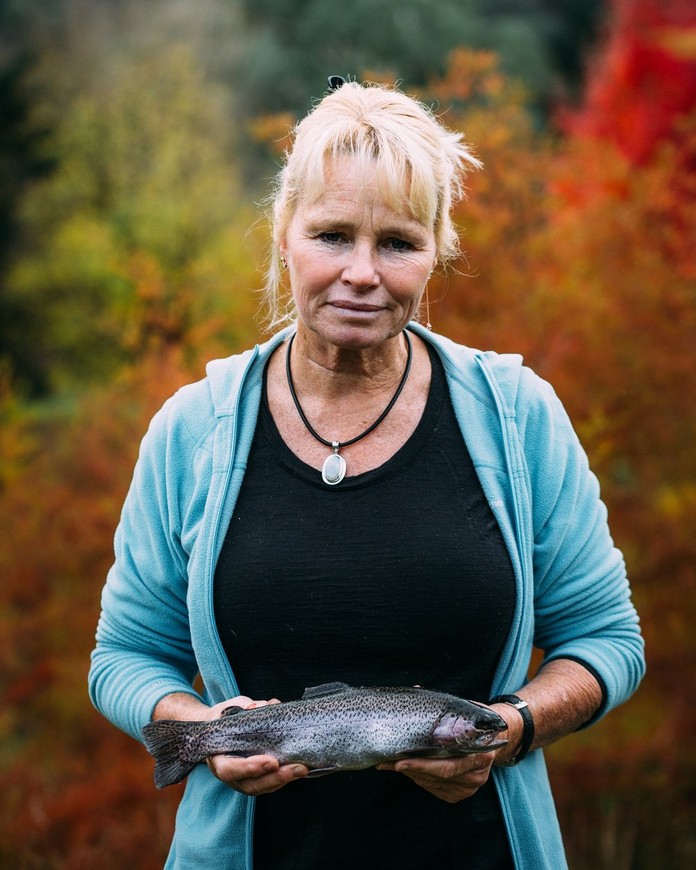 Sally Hall holding a trout on her farm, Mountain Fresh Trout and Salmon Farm, Harrietville (Victoria), 2017, Photographer: Catherine Forge, Source: Museums Victoria.