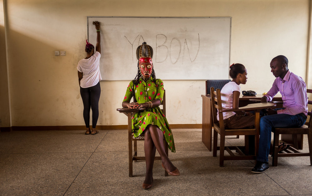 In a classroom at Accra University, Jacqueline wears a queen mask from the Baule, a people who three hundred years ago moved from what is now western Ghana to what is now central Côte d'Ivoire.