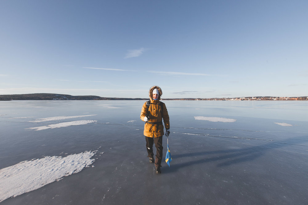 SIMK man walking on frozen lake with swedish flag