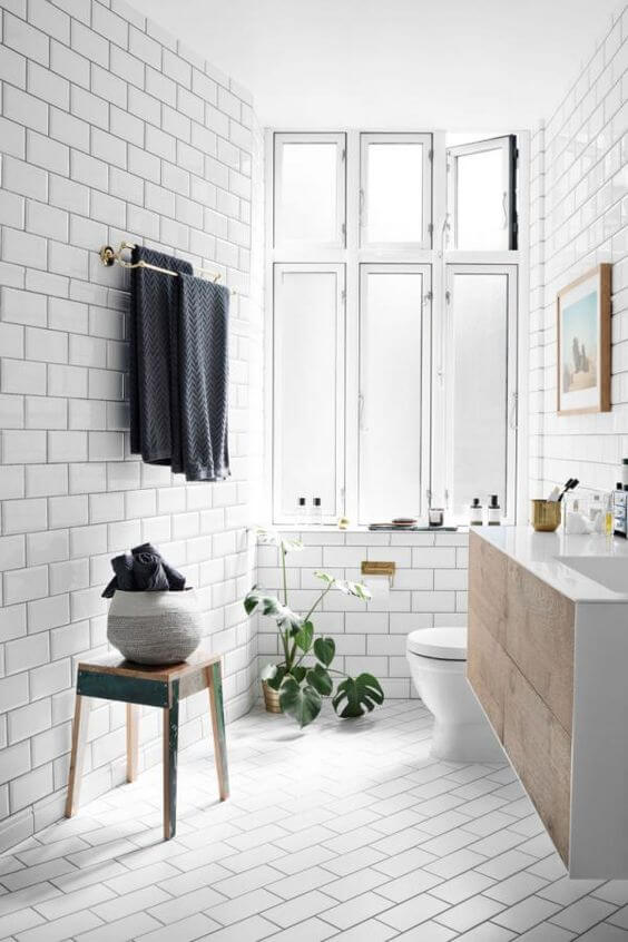 5. Crisp whites - All white tiles makes a bathroom feel crisp, fresh and clean. Laying your wall and floor tiles at a different angle gives a sense of depth and space. Having a large window in your fills the space with light!Image via Nordic Design