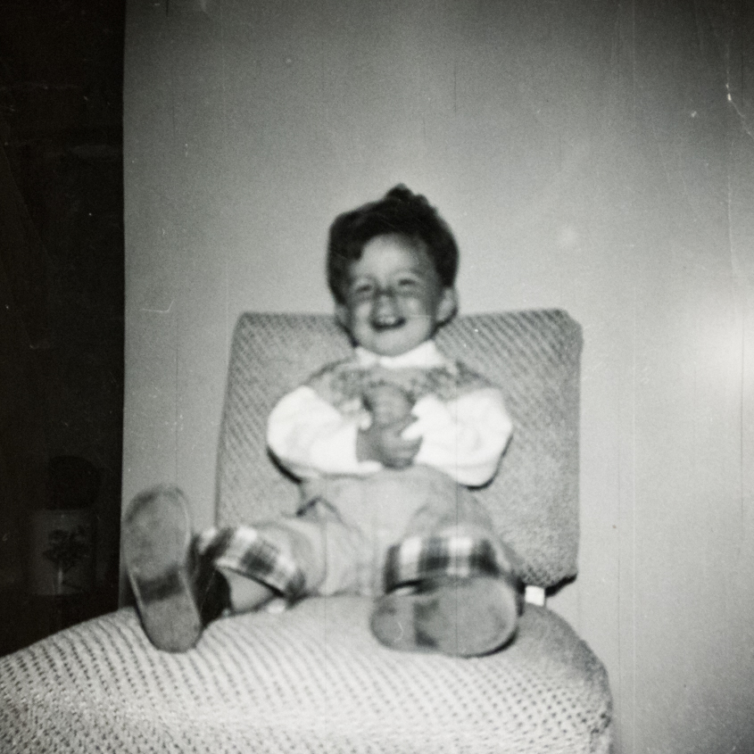 1954 Bruce aged two. Around this time. he lost much of his hearing after a bout with pneumonia and the prescribing of streptomycin. (Image: A smiling young boy with wavy brown wearing coveralls with the cuffs turned up to reveal a plaid lining while sitting back on a padded chair)