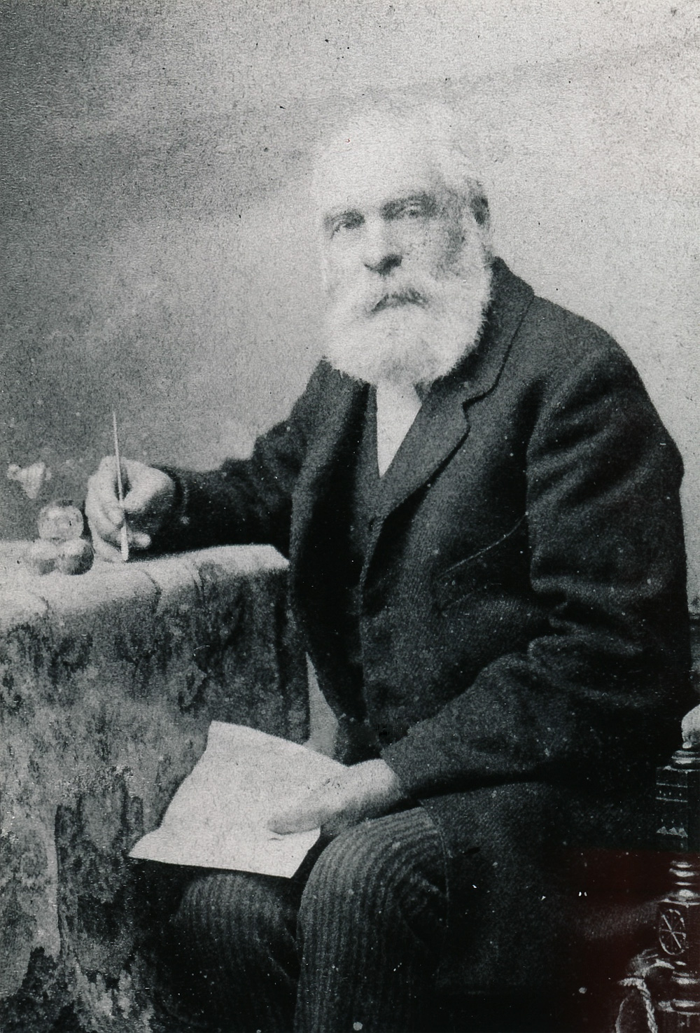 From the Glenbow Archives (Image: A period photograph circa 1890 of a seated older man with white hair and full beard holding a pen in his right hand a sheaf of papers in his left. He wears a tweed jacket, vest and striped trousers.)