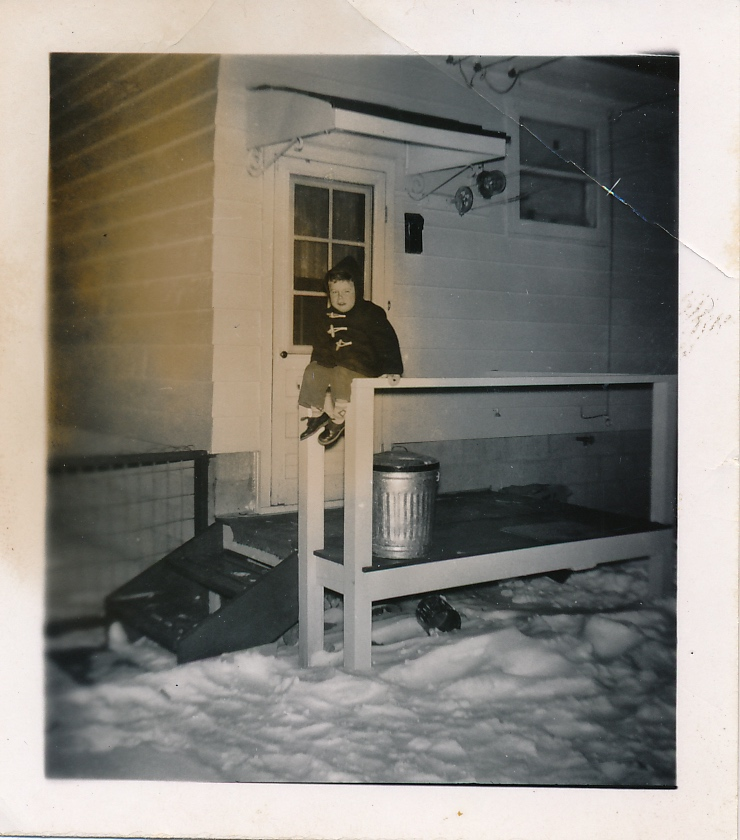 1955 Bruce aged three on the back porch of the new house at 7403 - 21A St. S.E. in Ogden on the outskirts of Calgary. (Image: A young boy in a dark-coloured parka sitting somewhat precariously on a porch railing of a small house in the background with snow covering the foreground.)