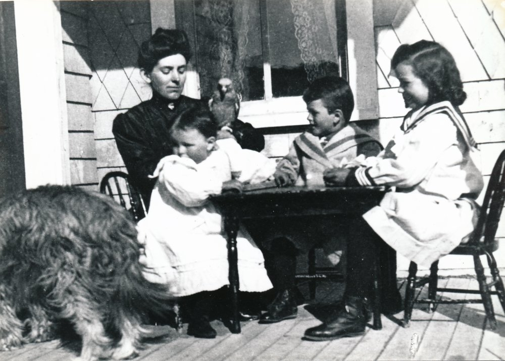 From the Glenbow Archives (Image: Lavinia Begg with her three children on the back porch of the ranch house at Dunbow, left to right, Lavinia Jr., Sandy and Norah. On Lavinia Sr.'s arm is Joe, her African grey parrot. She's wearing a high-necked blouse, the children all wear the same outfit: long sailor-type blouses with button-up boots. The children and the parrot seem fascinated by Mike a curly-haired dog with his hindquarters to the camera who seems to be eating,)