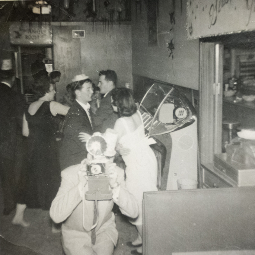 (Image: party-goers dancing, some wearing party hats. In the background is a juke box and in the foreground, a photographer horses around and aims his camera with a flash bulb at the photographer.)