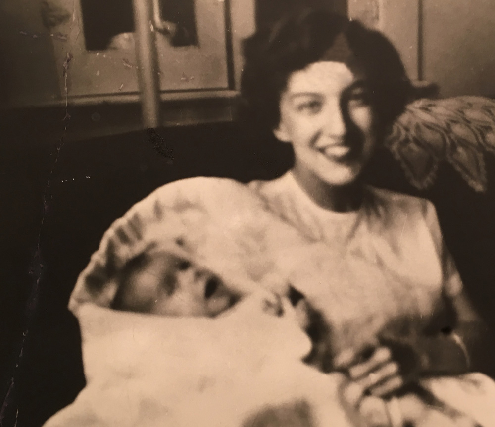 June 1952, 17-year old Joyce Hunter with her baby Bruce. (Image: A smiling young woman holding a very young baby swaddled in a white blanket).