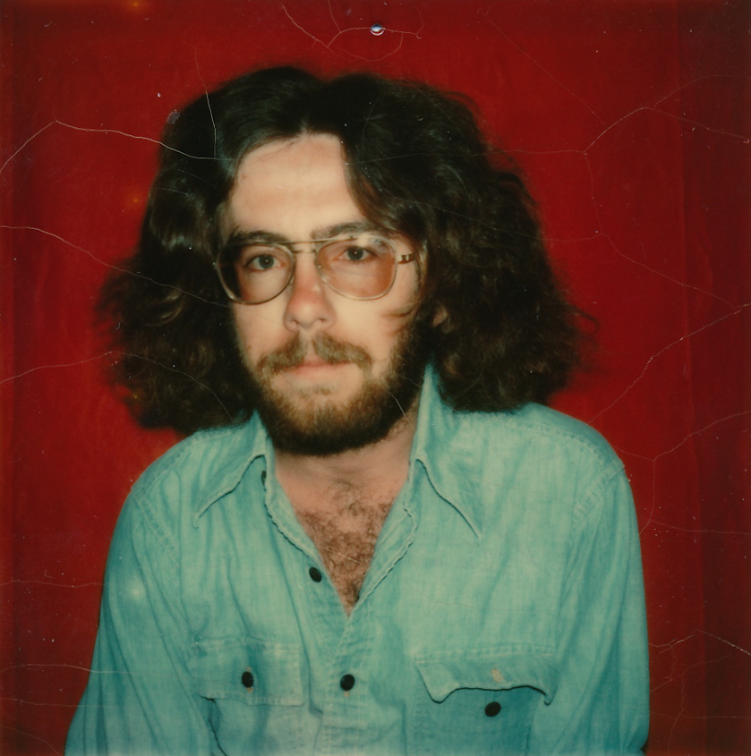 (Image: A colour photograph against a burgundy background of a young man, early twenties with shoulder-length wavy brown hair, thick beard and moustache, wearing tinted aviator lenses and a faded denim work shirt open at the neck.)