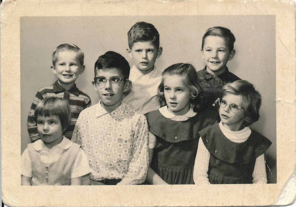 (Family photo against a plain white background. From left to right on the bottom row is Shirley Ann, a young red-haired girl, Bruce aged 12 in glasses with binaural temple-mount hearing aids, Susan with long blond hair, Maureen with cat's eyes glasses and shorter hair. In the back row, a smiling Terry, serious Mike and grinning Allan.)
