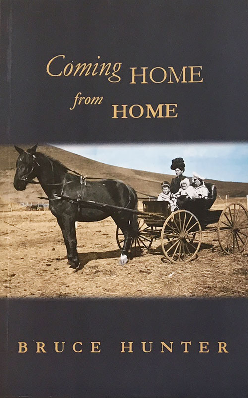 (Image: Slate-coloured cover of  Coming Home From Home  with colourised period photograph of a woman driving a horse and buggy with three children in it.) See family photos for a description of the original.