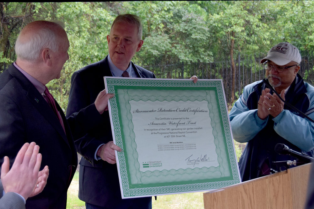 Department of Energy & Environment Director Tommy Wells presents a certificate for Stormwater Retention Credits to the Anacostia Waterfront Trust for its green infrastructure project.