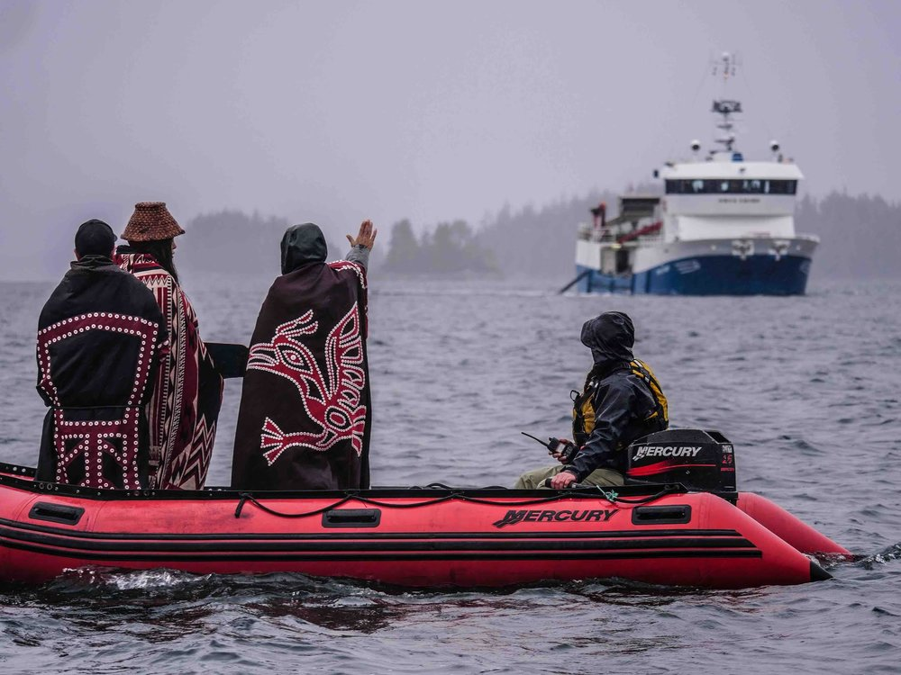 Members of the 'Namgis First Nation stand in protest of a ship transferring one million Atlantic salmon smolts to Marine Harvest's Swanson Island Farm.  Days before this photo was taken, the Canadian Federal Court dismissed the First Nation's court bid to block the restocking of the open-net salmon farm in its traditional territories off northern Vancouver Island, claiming that the 'Namgis had filed their application 'too late', but admitting that there was a 'real and non-speculative likelihood of harm' from the net pen operation. Photo by: Alexandra Morton