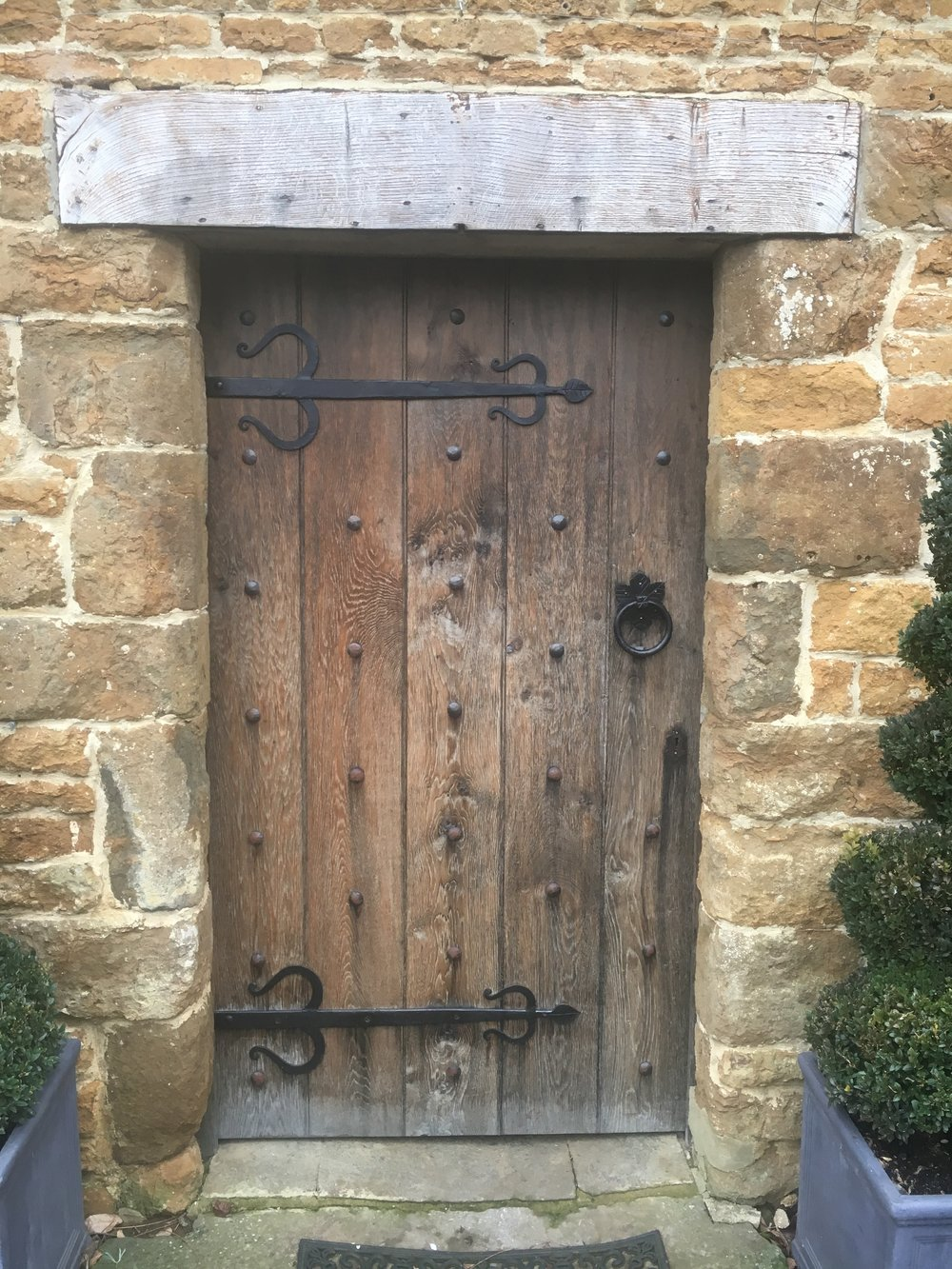 Aged English oak front door. Ironwork also designed by GFW, made by local blacksmith.