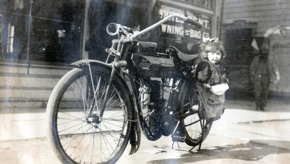 Lovely shot of a Thor single with a child in the saddle bag. Note the lack of headlight on this bike. At the time some brands offered motorcycles without headlights as an option.