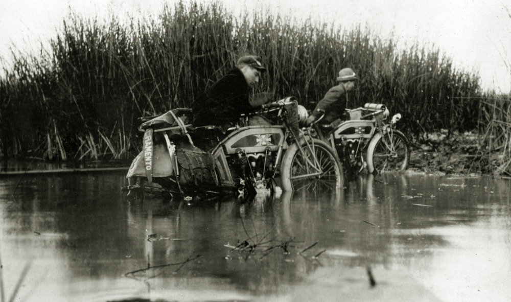 "Riders crossing a creek near Slough House east of Sacramento. Roads were very primitive in this period. Note that these are not what we would call today ""Adventure Motorcycles."" In this period all motorcycles were adventure bikes. Which kind of puts the lie to the whole myth that you need to have a special motorcycle to go off road. Really all you need is determination."