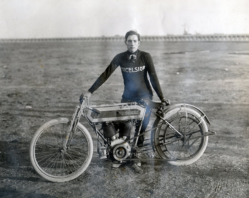 An unknown rider posing with his belt drive Excelsior at Agricultural Park in Sacramento during race week in 1912.