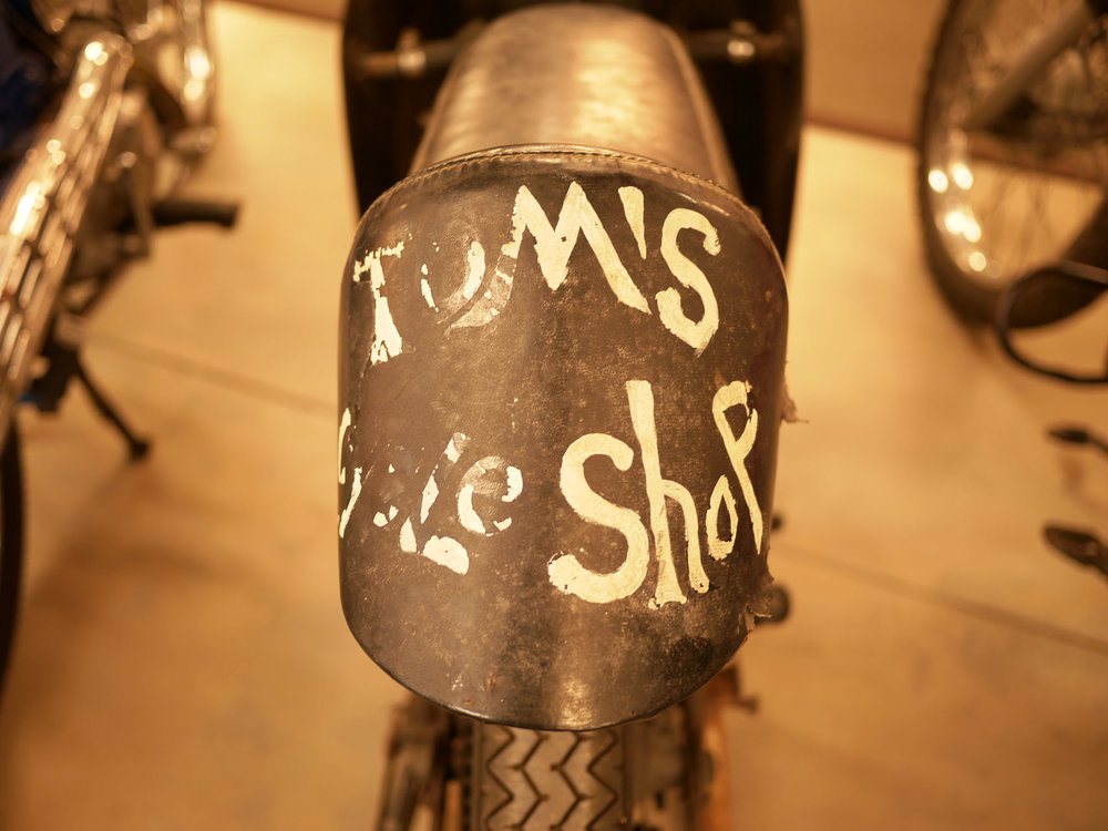 "fantastic patina on the Tom's Bike Shop Steen Aermacchi/Hodaka road racer. It is great that the collection is willing to let bikes have their history. It would be a crime to ""restore"" this bike."