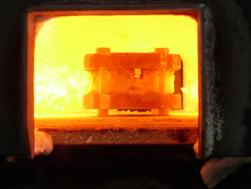 Fig. 1:  Billet in the forge: note the small observation window in the coating on this billet. Color and other changes in the metal can be seen here.