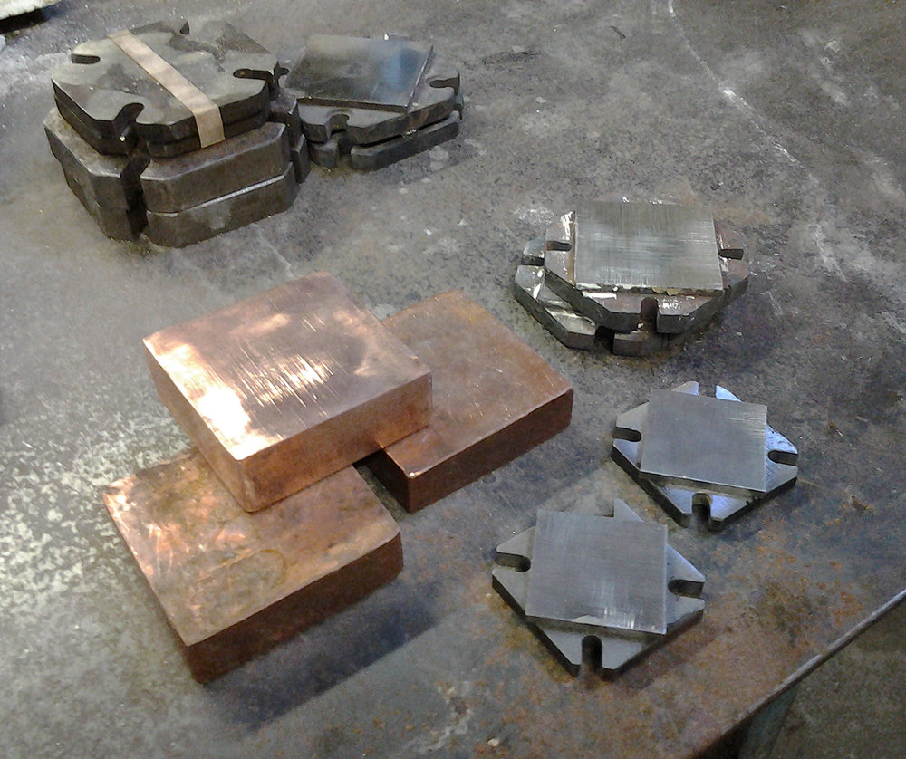 Fig. 3:  Torque plates and copper cooling blocks. Slots in the plates allow easy removal of  bolts after hot pressing. Note the smaller square pads that make for easy flat grinding.