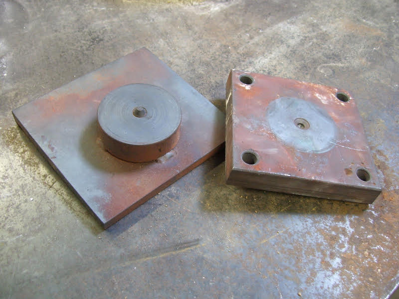 Fig. 6:  Turntable on the left fits on the forge floor. At the right, the upside down torque plate engages the pin on the turntable.