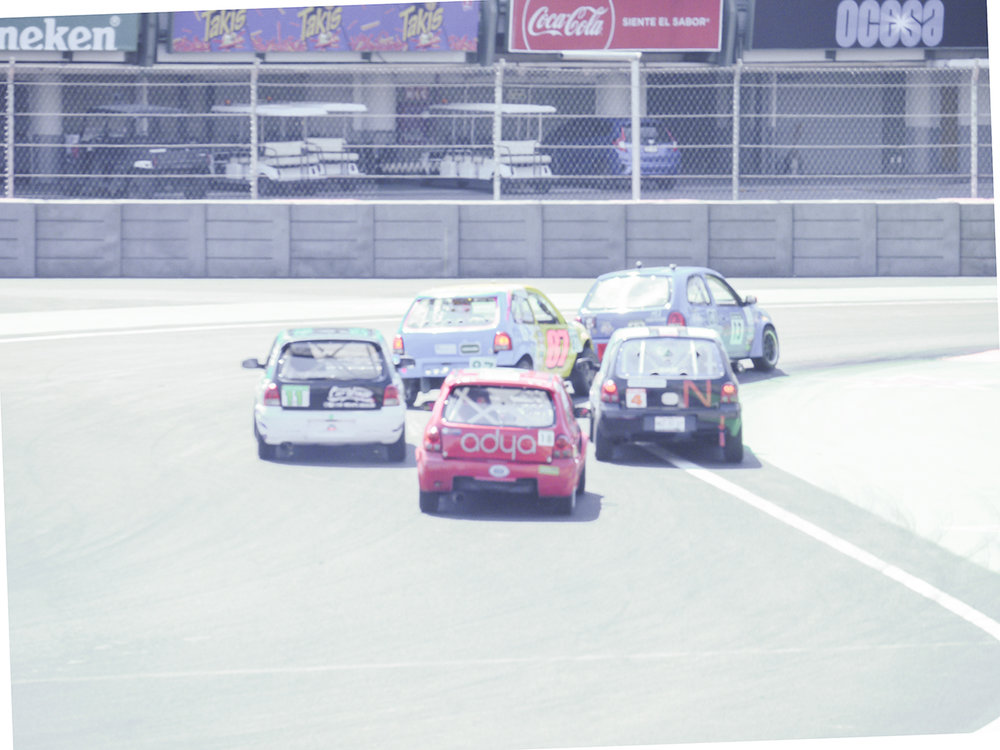 De Rivas holds off four fellow racers heading towards the pit straight.
