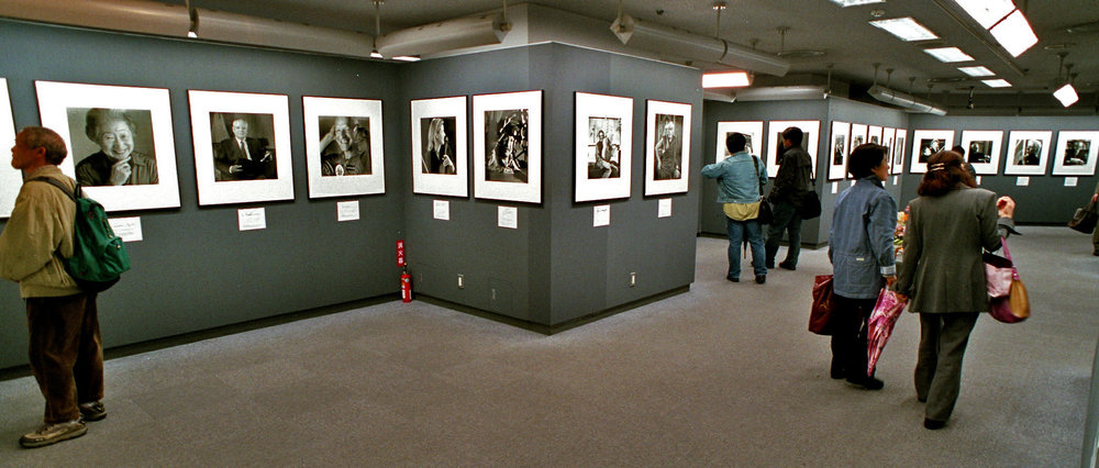 """A view of the exhibit at the Fuji Photo Salon that accompanied the publication of """"Swiss Guest Book"""". Phändler says of the show, """"The exhibition was part of the Frame-Program of the World Exhibition in Japan 2005-2006. The Swiss Embassy was the patron of the frame program as a complimentary exhibition to the exhibits in the Swiss Pavilion. I refused to have my images shown there because the size would have been too small and the series not numerous due to lack of space. Funny enough, I got sponsored by the government for my exhibition and they bought  Swiss Guest Book  later to bring as presents from Switzerland on international state visits. On a flight I coincidently met the president of Switzerland on board and he told me, that he personally brought my  Swiss Guest Book  at least 10 times as a present to foreign countries as a state gift."""""""