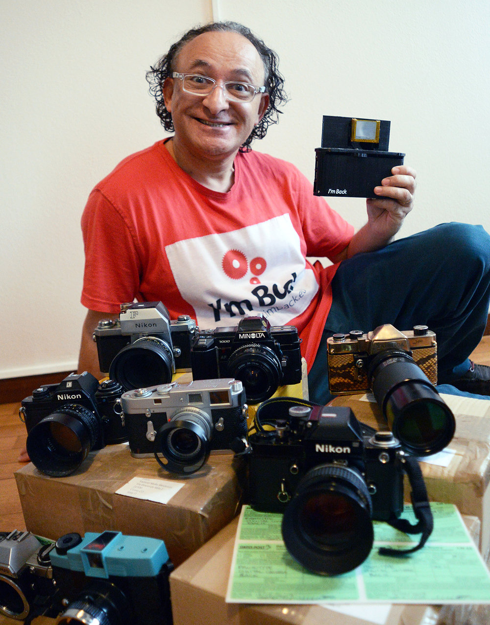 Designer and inventor Samuel Mello Madeiros with his collection of film cameras and the digital back he designed for them.