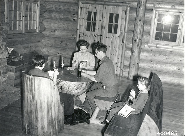 A_family_group_playing_cards_in_the_Community_Building_on_a_rainy_day_at_the_South_Kawishiwi_River_camp_and_Picnic_Ground,_8_1_1940_(5188124888)